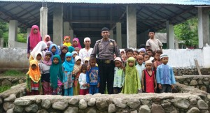 Caption foto: Bripka Junaidin, petugas Polisi Polsek Rasanae Barat, kota Bima, bersama dengan anak-anak dan pembimbing pondok pesantren Al Fathul Alim, ponpes yang dia dirikan sendiri di desa Songgela, kota NTB, Rabu (10/2) lalu. foto: Tri Mujoko Bayuaji/Jawa Pos