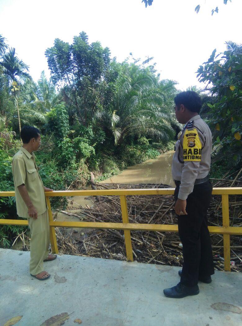 Bhabinkamtibmas cek tiang jembatan yang roboh bersama Kades